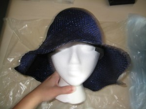 The hat must remain wet and pliable for the rest of the shaping, or it will tear, splinter, and generally not become a hat.  Place the hat onto the head, and tug gently but firmly until it's sitting evenly like a proper hat being worn.  You're stretching the hat to accommodate a head and shaping the crown (top bit) in this step. I find that a sort of thumb-massage motion works well for getting any weirdness out of the shape.