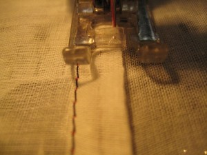 You can see I'm lining up the right corner of the triangle guide on my machine's foot with the folded edge, to keep my stitches nice and straight.