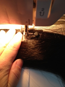 I cut the hanks of hair in half.  I'm sewing down the middle of each half-hank, with a strip of interfacing between the hair and the machine.
